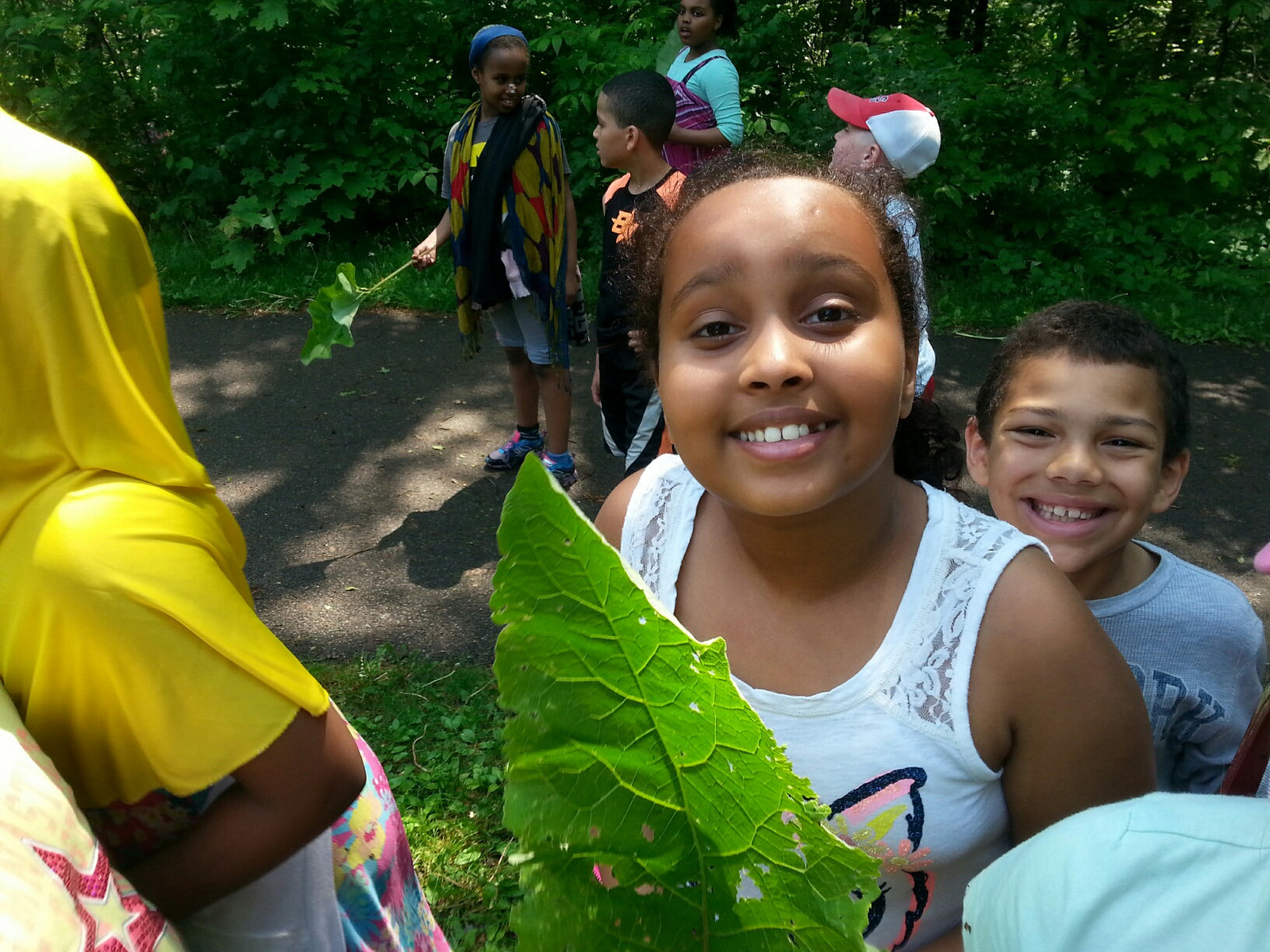 A few younger River Gorge Stewards remove garlic mustard and burdock (with big-enough leaves that double as fans.
