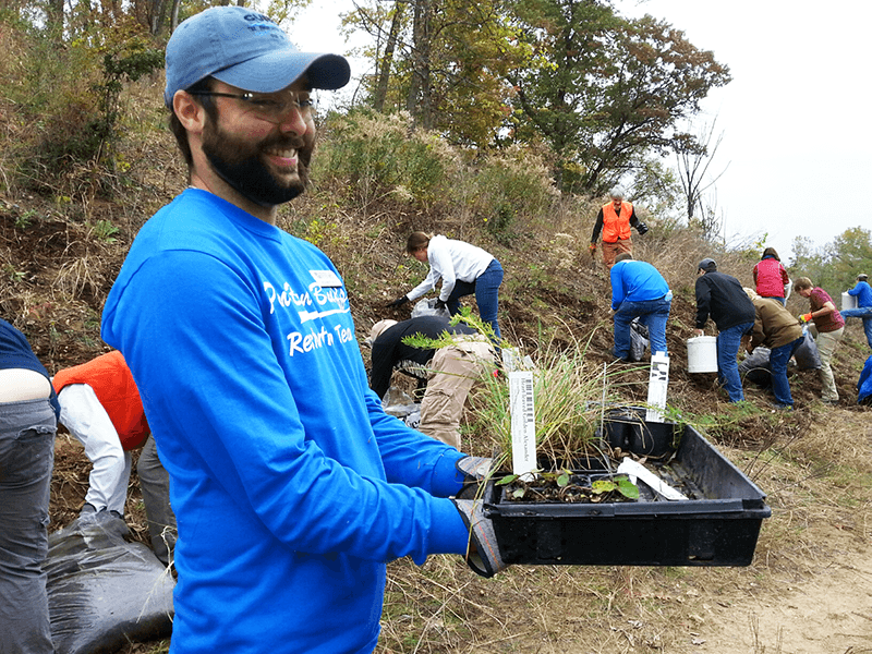 Adam Flett holds a tray of plants at a stewardship event
