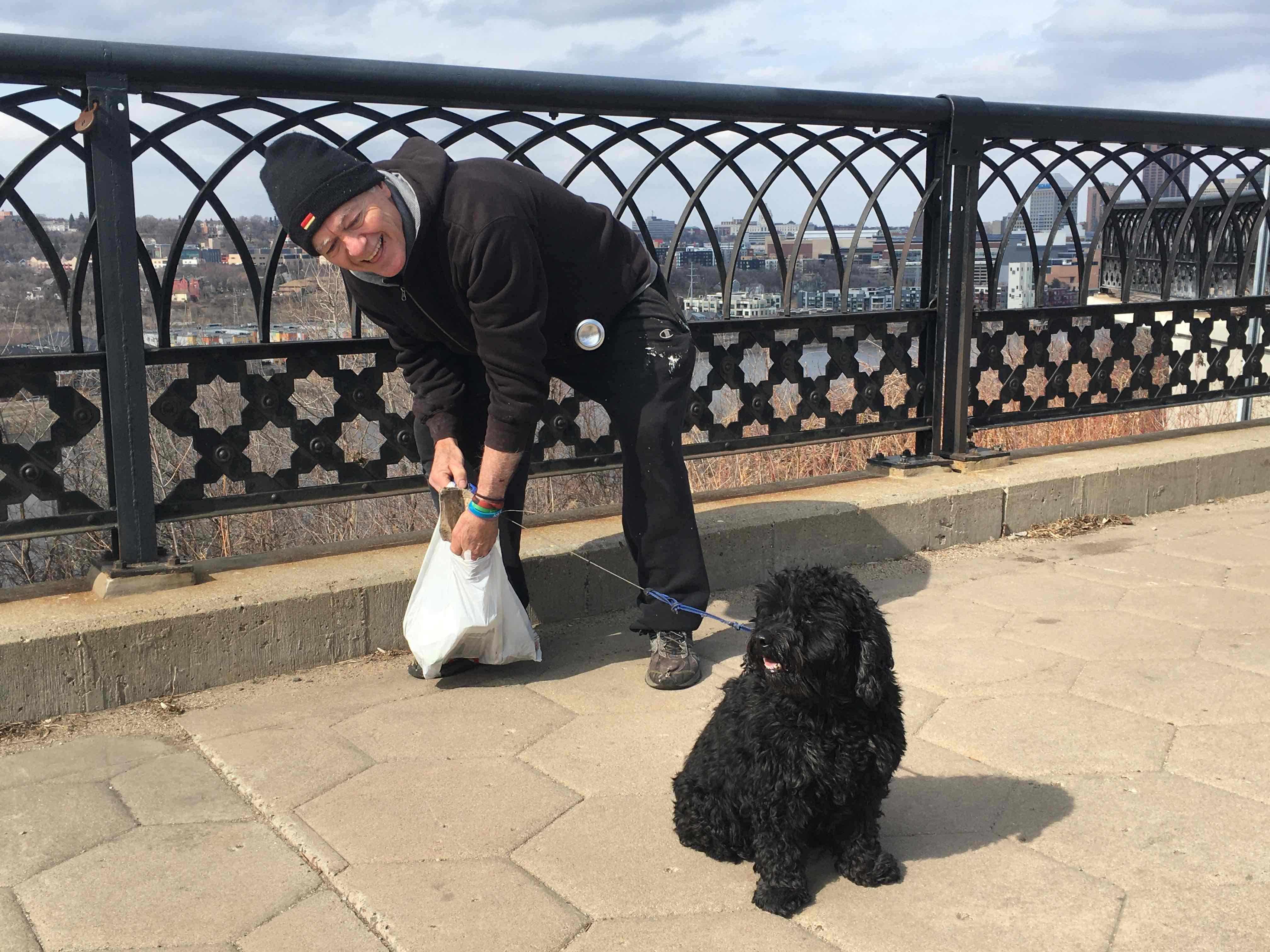 Nico the dog and his human pick up trash on a bridge over the Mississippi