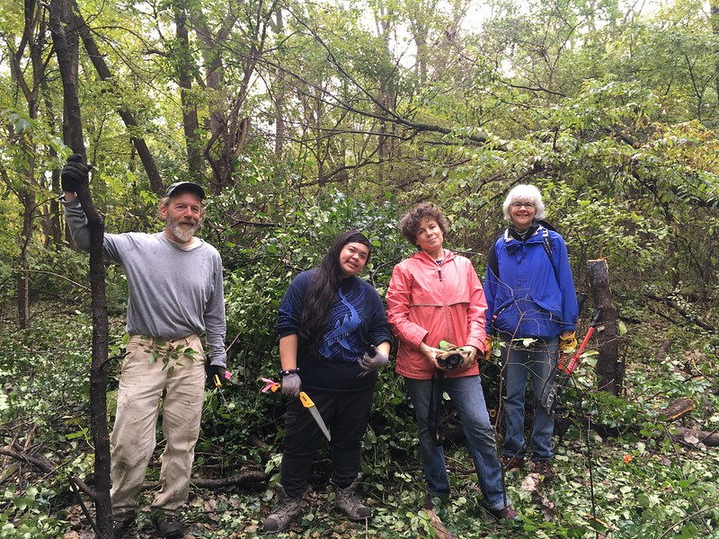 A team of four poses in front of the brush pile they've created.
