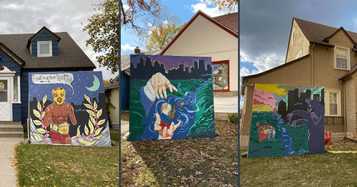 Three large murals with images of community displacement stand in yards