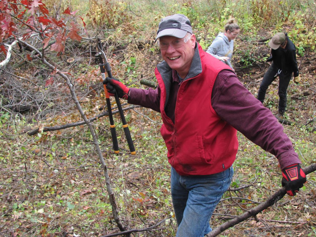 Volunteer with lopper and buckthorn in hand