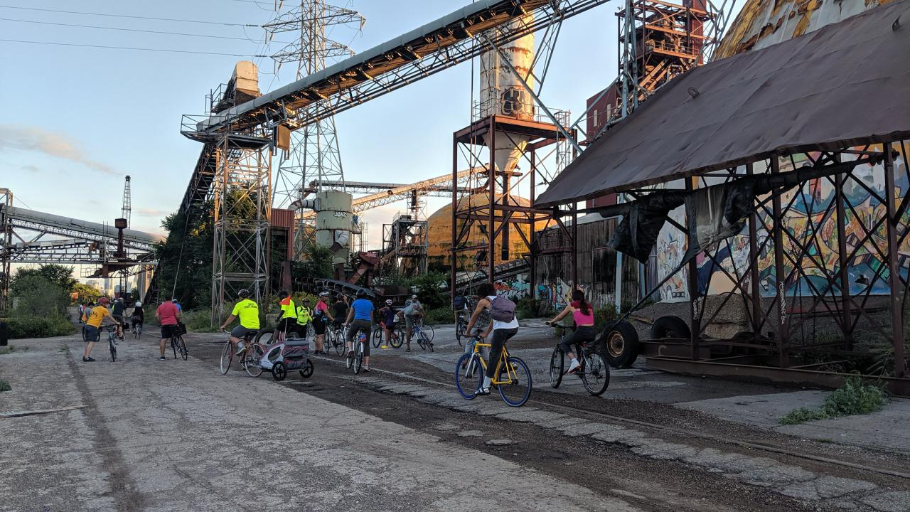 Bicyclists ride among abandoned industrial structures at the Upper Harbor Terminal site.