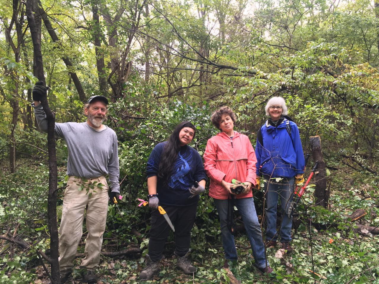 Volunteers pose in front of cut buckthorn in the river gorge