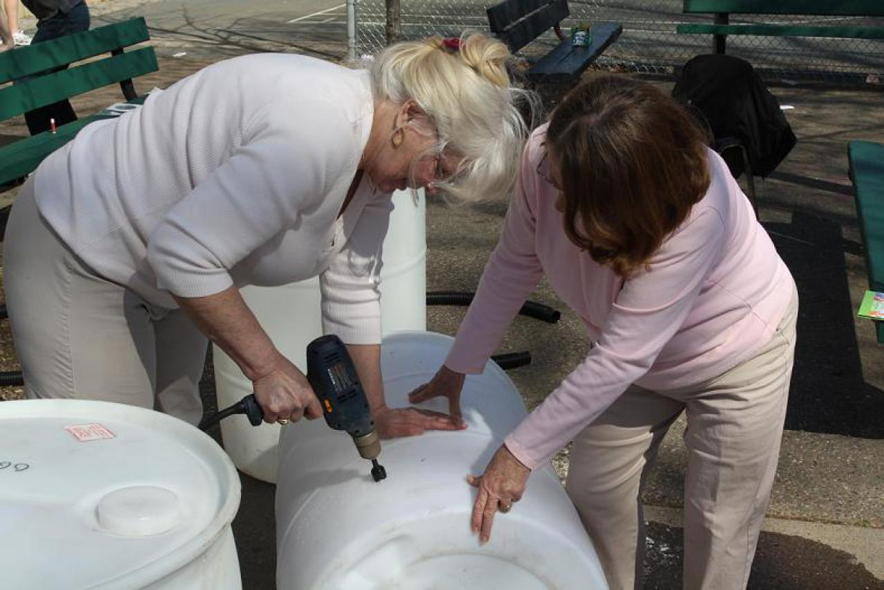 Two rain barrel builders work together at a workshop