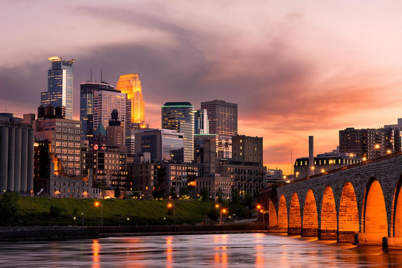 Downtown Minneapolis glows along the Mississippi at the end of the Stone Arch Bridge.