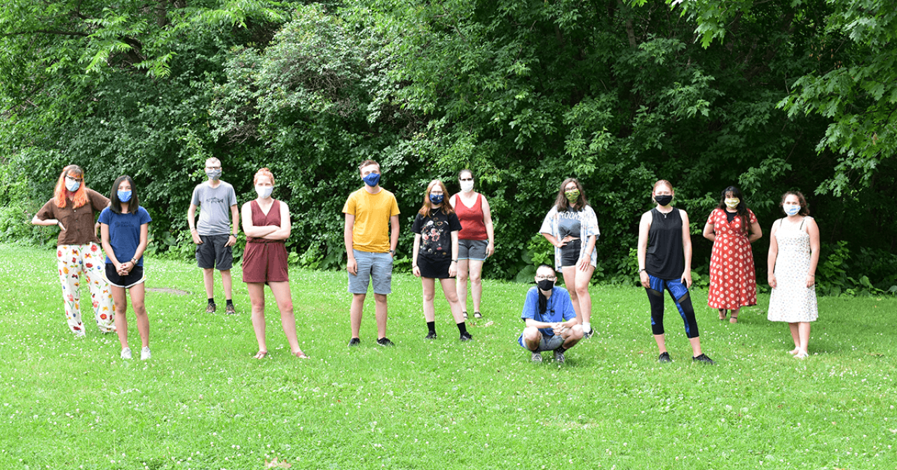 Program participants stand in grass