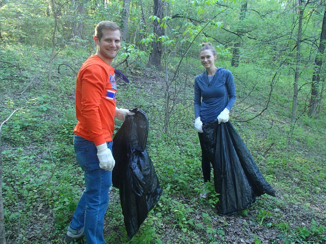 Two volunteers removing invasive species, bag in hand.