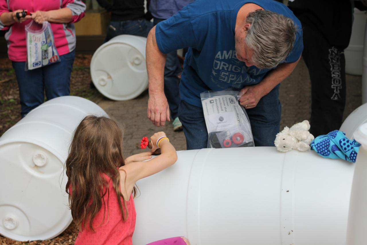 Workshop participants assembling a rain barrel