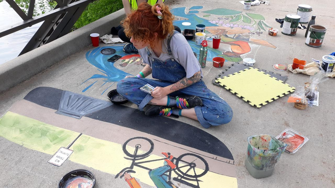 Artists work on the 2019 stormwater mural at Lake Phalen
