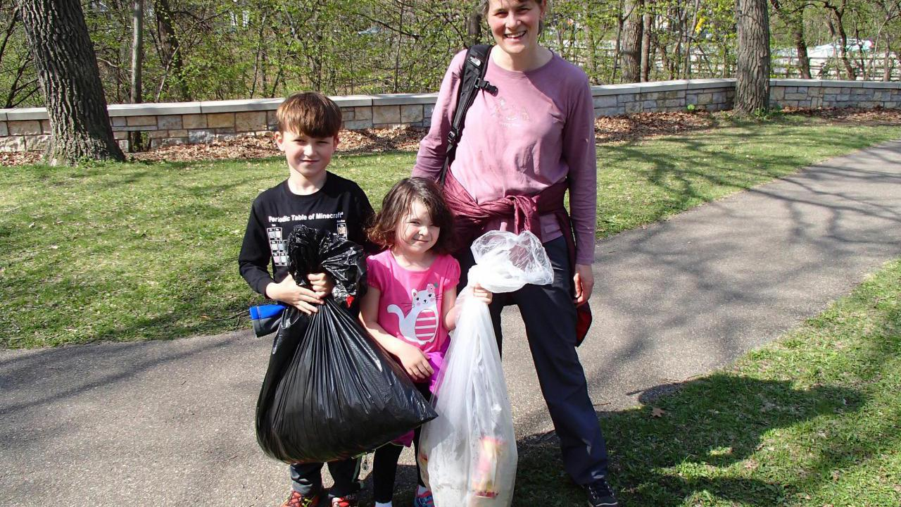 A family with their haul of litter and recyclables at the Earth Day cleanup