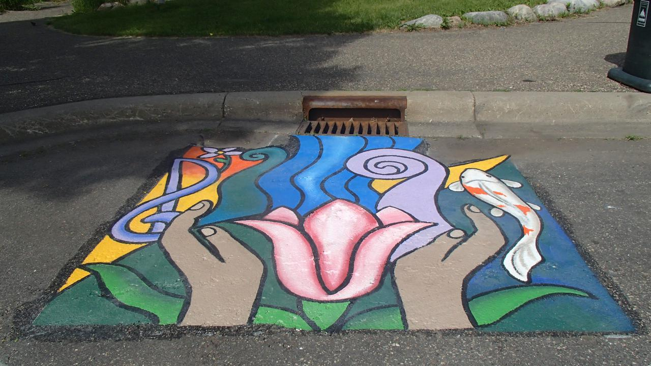 Storm drain mural contains music and fish to connect it to como park and hands representing our responsibliity to care for the lake